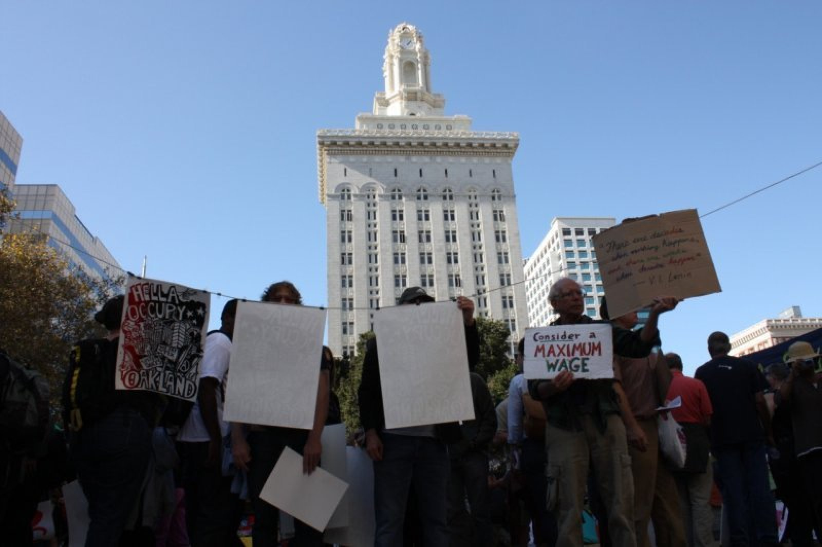 People looking at posters in front of Oakland\'s city hall. Photo: Rosa Ramirez